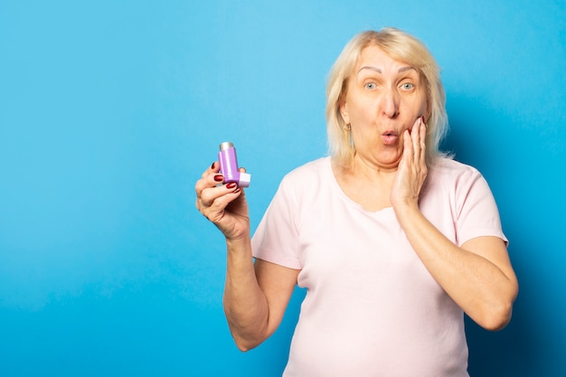 Portrait of an old friendly woman with a surprised face in a casual t-shirt holds an inhaler on an isolated light wall. emotional face. asthma, allergy concept