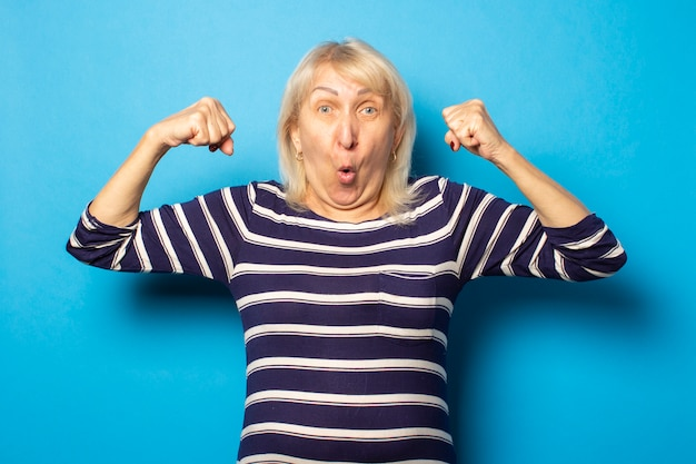 Portrait of an old friendly woman with a surprised face in a casual t-shirt makes a bodybuilder gesture on an isolated blue wall. emotional face. gesture strength, power, good health