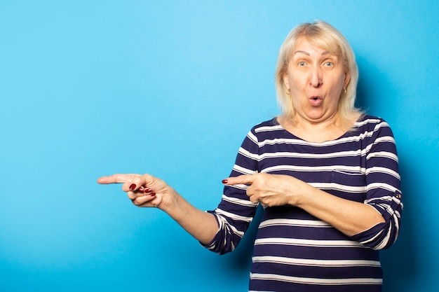 Portrait of an old friendly woman with a surprised face in a casual t-shirt points her hands to the side on an isolated blue wall. emotional face. gesture pay attention to it, look at it