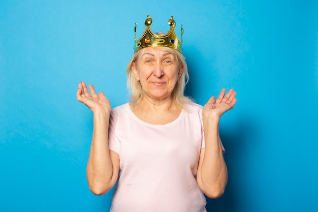 Portrait of an old friendly woman with a surprised face in a casual t-shirt with a crown on her head on an isolated blue wall. emotional face