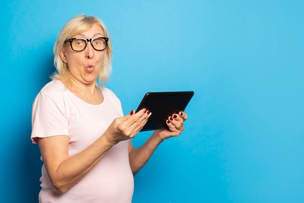 Portrait of an old friendly woman with a surprised face in glasses and an casual t-shirt holding a tablet in her hands on an isolated blue wall. emotional face