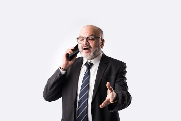 Portrait of old indian asian businessman using smartphone for messaging, calling or showing or presenting against white background