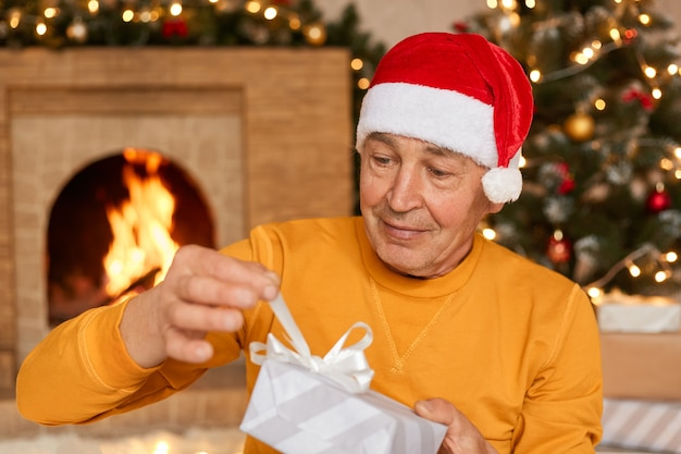 Portrait of old male in santa claus hat and yellow jumper opening gift box with white ribbon, looking at his present with interest, posing on background of fireplace and christmas tree.