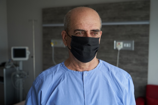 Portrait of an old man, 70 years old, in a medical mask