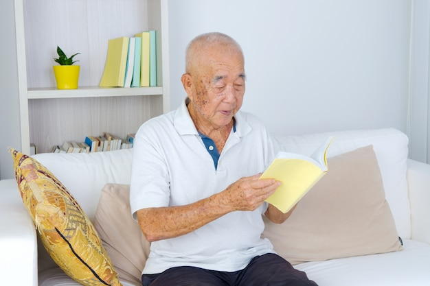 Portrait of an old man reading a book