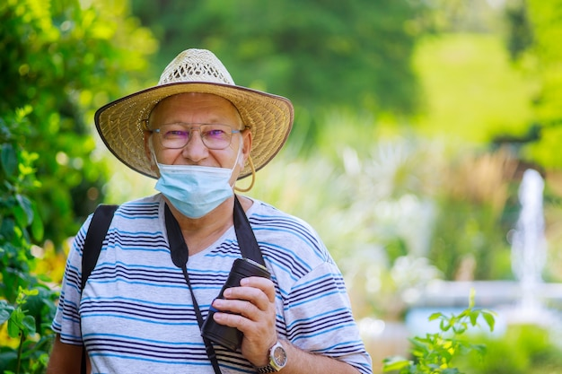 Portrait of an old man a wearing medical mask protect during coronavirus in a park
