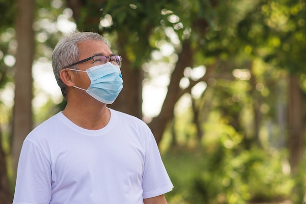 Portrait of old man wears surgical mask in a park outdoors
