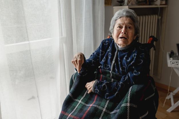 혼란 스 러 워 얼굴로 집에서 휠체어에 앉아 초상화 오래 된 아픈 여자. 세 번째 나이, 가정 노인 지원 개념.