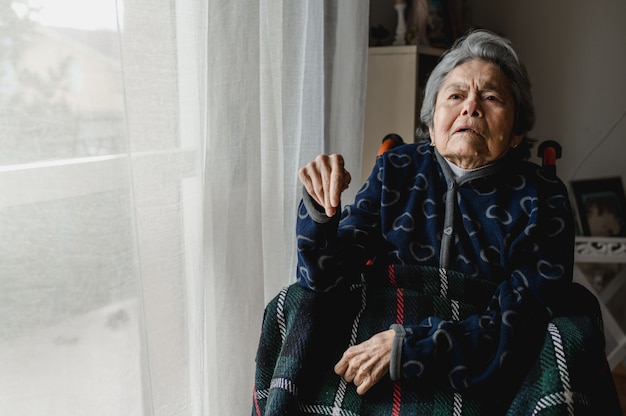 Portrait old sick woman sitting in wheelchair at home. third age, home elderly assistance concept.