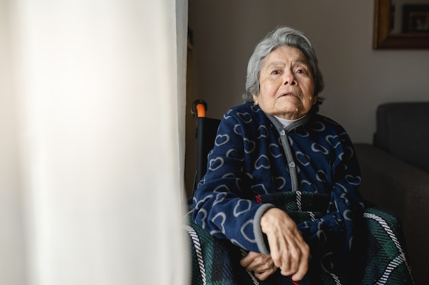 Portrait old sick woman sitting in wheelchair at home with disoriented, confused face.. third age, home elderly assistance concept.