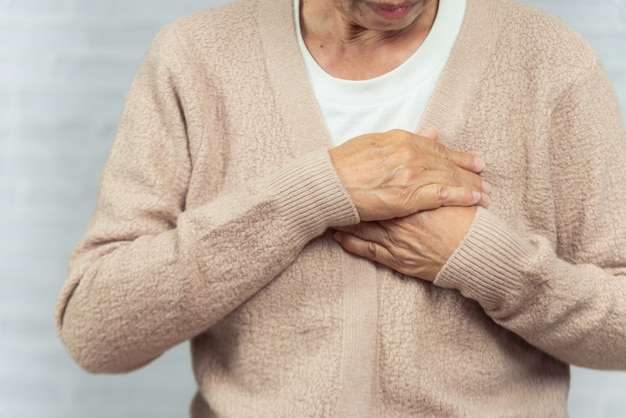 Portrait of old woman holding breast because of heart infarction on gray