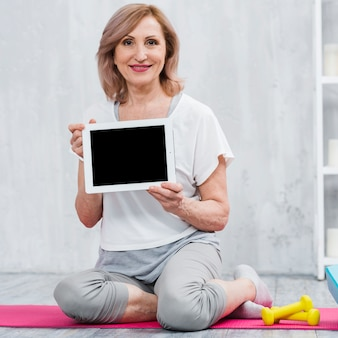 Portrait of a old woman sitting on yoga mat holding digital tablet in hand