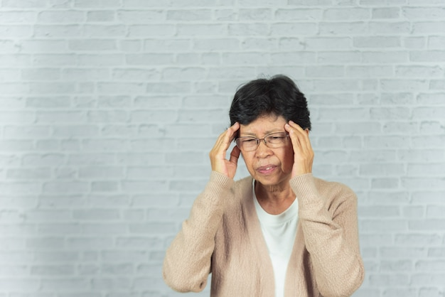 Portrait of old woman with headache on gray