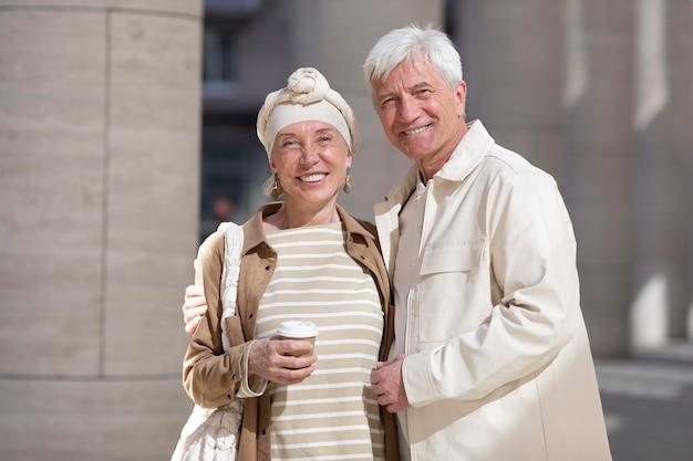 Ritratto di coppia di anziani all'aperto in città con una tazza di caffè