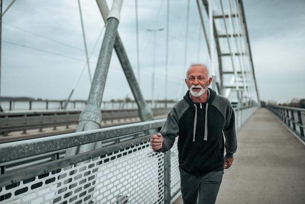 Portrait of older male runner running outside.