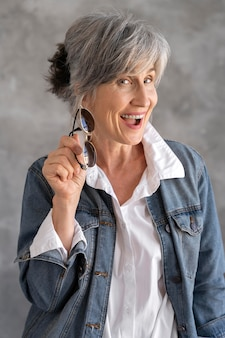 Portrait of older woman posing in a jean jacket and holding sunglasses