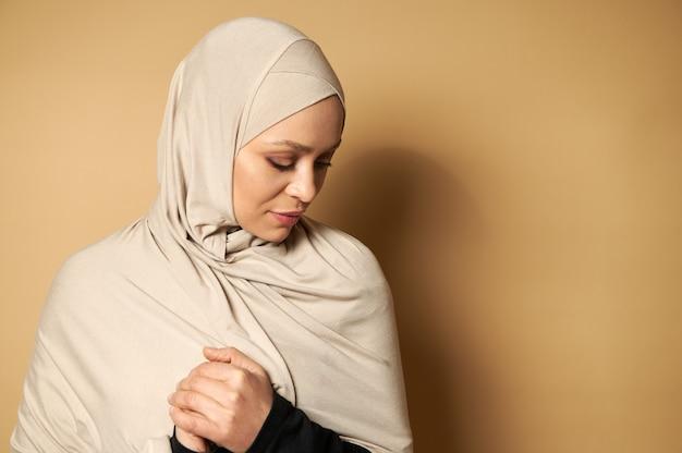 彼女の前に彼女の拳を持って見下ろしている美しい穏やかなイスラム教徒の女性のコピースペースとベージュの表面の肖像画