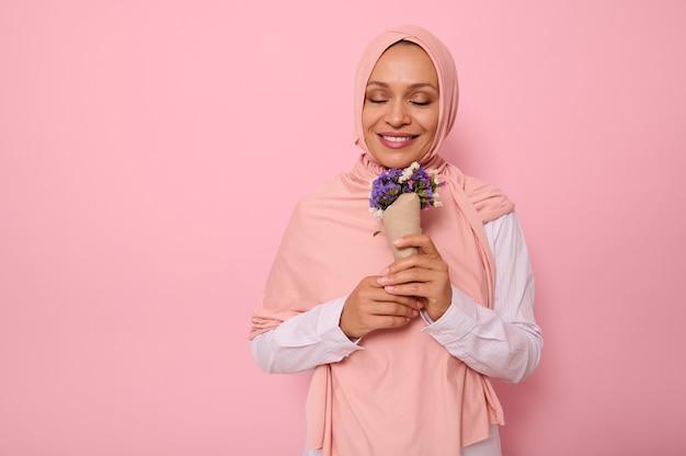 目を閉じて、クラフト紙に包まれた牧草地の花の香りを楽しんでいる魅力的な笑顔でヒジャーブのゴージャスなイスラム教徒のアラブの女性のピンクの背景の肖像画。国際女性デーのコンセプト