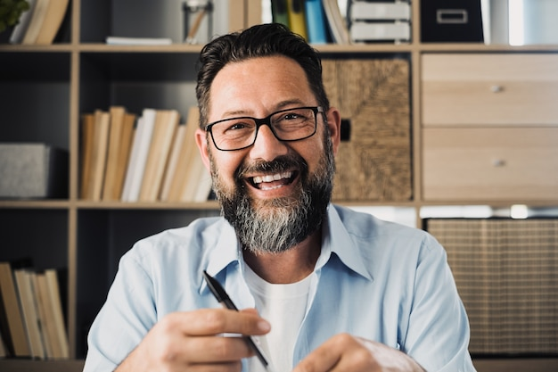 Portrait of one happy cheerful artist man looking at the camera taking inspiration to draw or paint at home. businessman in the office working and smiling