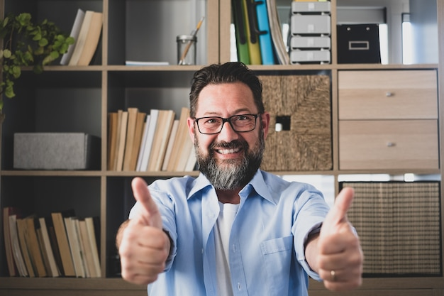 Portrait of one happy and cheerful man smiling and looking at the camera with finger's hand up. male person businessman having fun after receive good news of work