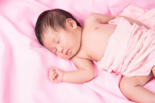Portrait of a one month old sleeping, newborn baby girl on a pink blanket