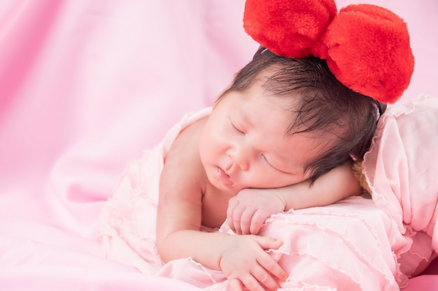 Portrait of a one month old sleeping, newborn baby girl. she is wearing a red hair band and sleeping on a pink blanket. concept portrait studio fashion newborn.