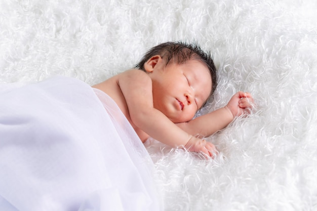 Portrait of a one month old sleeping, newborn baby girl on a white blanket