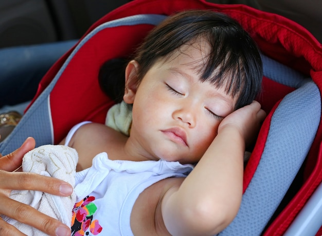Portrait of one year and six month year old cute asian baby girl sleeping in car seat