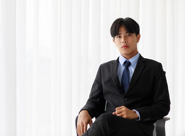 Стул костюма портрета одного молодого азиатского бизнесмена нося сидя пока чувствует уверенно с усмехаться как улыбка на лице смотря камеру с окном на предпосылке. в концепции бизнесмена нового поколения.