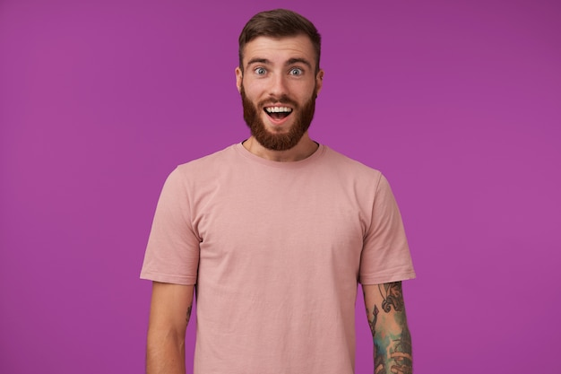 Portrait of onjoyed young bearded brunette man with tattooes wearing beige t-shirt and trendy accessories, standing on purple with hands down and wide mouth opened