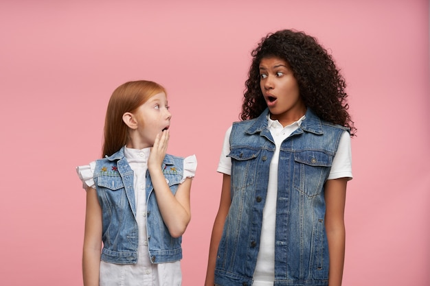 Portrait of onwhelmed young girls with long hair keeping eyes wide opened while looking amazedly on each other, posing on pink in casual clothes