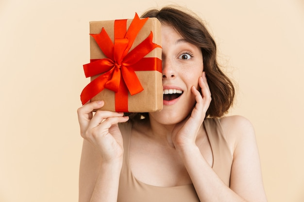 Portrait of optimistic caucasian woman 20s dressed in casual clothes smiling while holding present box isolated