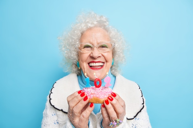 Portrait of optimistic curly haired woman holds delicious doughnut in hands smiles broadly has red nails enjoys birthday celebration blows number candles
