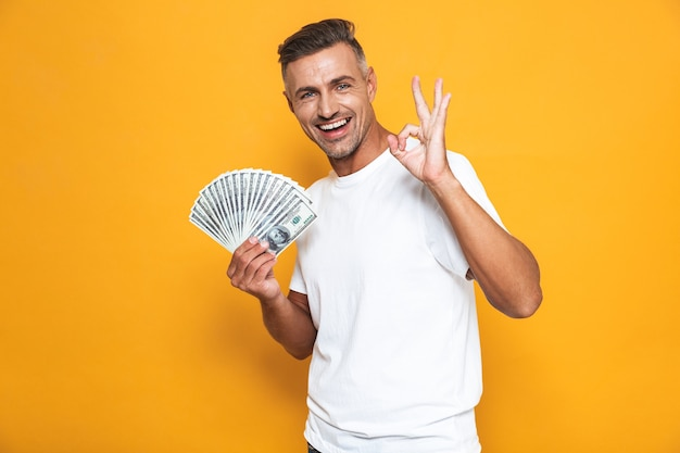 Portrait of optimistic guy 30s in white t-shirt smiling and holding bunch of money isolated on yellow