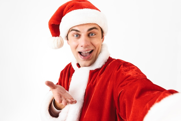 Portrait of optimistic man 30s in santa claus costume and red hat laughing while taking selfie photo
