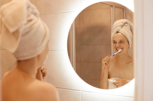 Portrait of optimistic winsome woman brushing her teeth, having hygiene procedures after taking shower in bathroom, standing with white towel on her hair.