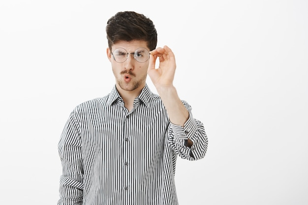 Portrait of ordinary adult european male student, taking off glasses and cleaning glass of eyewear, staring at goggles focused, folding lips to blow, standing over gray wall
