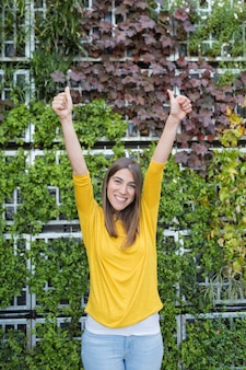 Portrait outdoors of a beautiful young woman with thumbs up and smiling. wearing a yellow casual shirt over .
