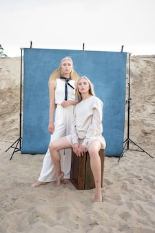 青い背景の前の砂の上の屋外の肖像画、長いブロンドの髪のポーズで若いかわいい双子