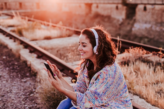 Portrait outdoors of a young beautiful woman at sunset listening music on headset and smiling