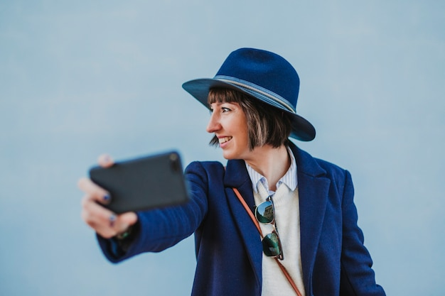 Portrait outdoors of a young beautiful woman with stylish clothes posing with a modern hat and taking a selfie with mobile phone. lifestyle