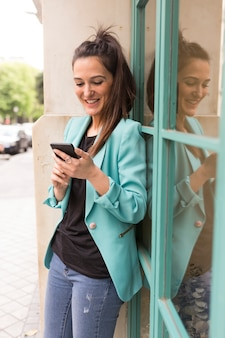 Portrait outdoors of young happy blogger woman with mobile phone. glass windows background. wearing casual clothes. fun and lifestyle