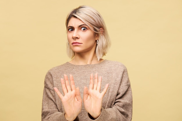 Portrait of outraged furious young european blonde woman expressing indignation, reaching out hands, making no or stop gesture, saying stay away from me while having fight with her boyfriend