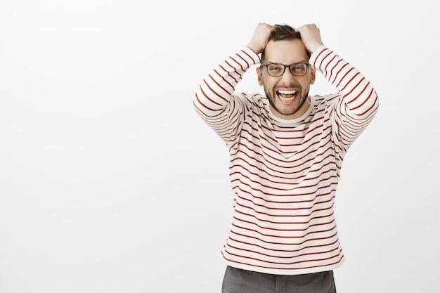 Ritratto di maschio caucasico indignato incazzato con gli occhiali, tirando i capelli fuori dalla testa e urlando di rabbia, essendo stressato e depresso, sentendosi arrabbiato e disperato per il muro grigio