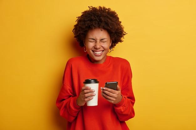 Ritratto di donna afroamericana felicissima prende appunti in smartphone