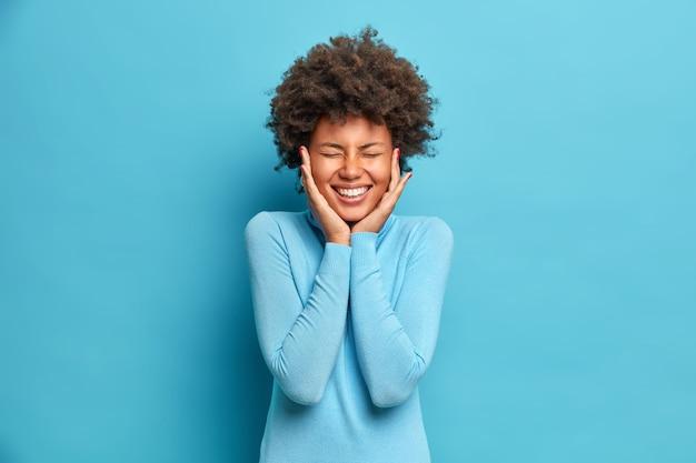 Il ritratto della donna afroamericana felicissima con i capelli ricci tiene le mani sulle guance sorride ampiamente