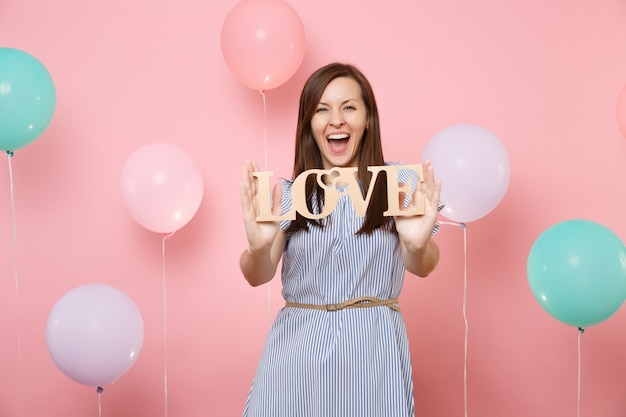 Portrait of overjoyed beautiful young woman in blue dress holding wooden word letters love on pastel pink background with colorful air balloons. birthday holiday party people sincere emotions concept.