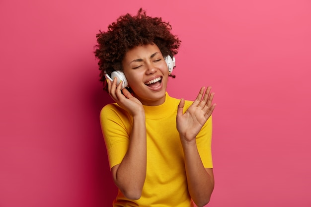 Portrait of overjoyed carefree woman listens music, sings songs wears headphones, closes eyes, forgets about all problems, wears yellow clothes, isolated on pink wall. lifestyle concept