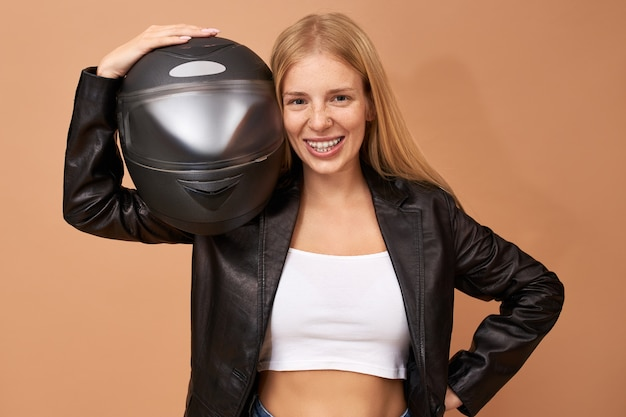 Portrait of overjoyed cheerful young female rider with teeth braces and long straight hair posing isolated in black leather jacket