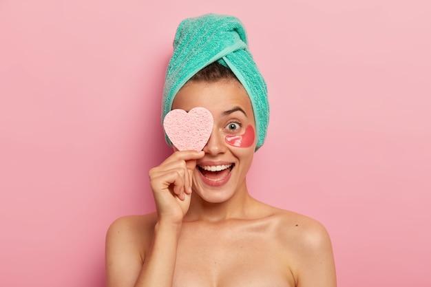 Ritratto di donna divertente e felicissima mantiene la spugna cosmetica sugli occhi, ride sinceramente, indossa cerotti sotto gli occhi, rimuove le rughe, si prende cura della pelle, ha una bellezza naturale